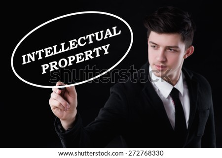 business, technology and internet concept - businessman is writing intellectual property text - stock photo