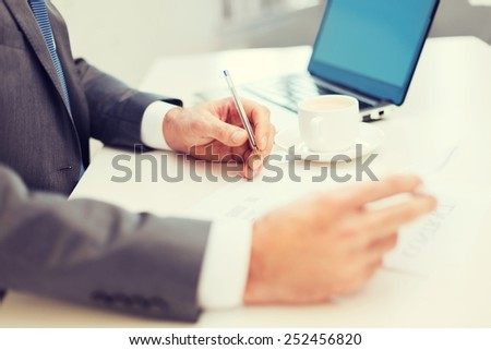 business, technology and internet concept - close up of man hands with contract and pen, coffee and laptop computer