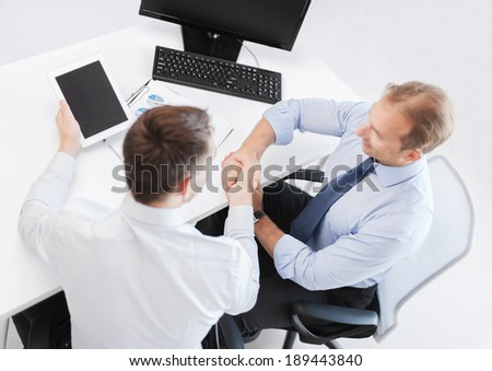 business, technology and office concept - businessmen shaking hands in office - stock photo