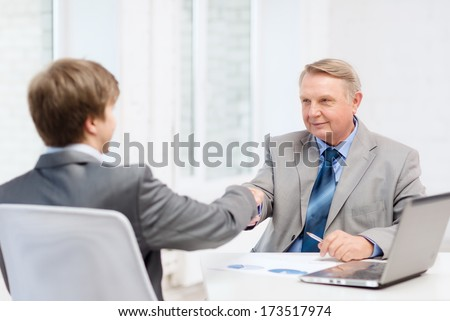 business, technology and office concept - older man and young man shaking hands in office - stock photo