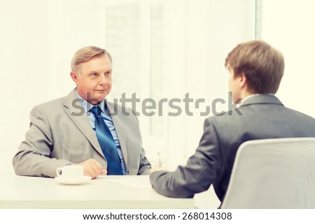 business, technology and office concept - older man and young man signing papers in office - stock photo