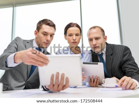 business, technology and office concept - serious business team with tablet pc computers, documents and coffee having discussion in office - stock photo