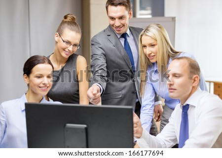 business, technology and office concept - smiling business team with computer monitor having discussion in office