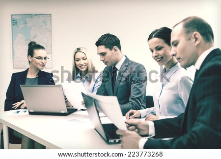 business, technology and office concept - smiling business team with laptop computers and documents having discussion in office - stock photo