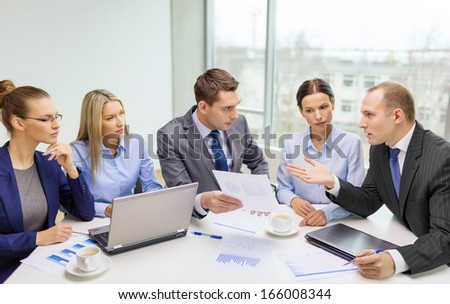 business, technology and office concept - smiling business team with laptop computers, documents and coffee having discussion in office - stock photo