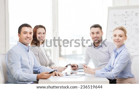 business, technology and office concept - smiling business team with smartphones having meeting in office - stock photo