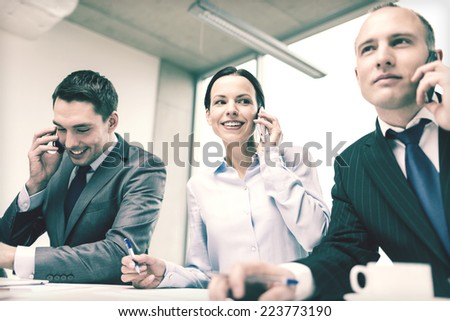 business, technology and office concept - smiling business team with smartphones making calls in office - stock photo