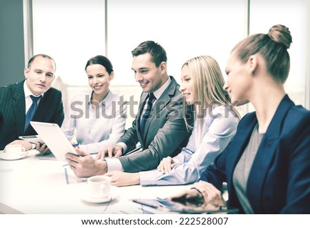 business, technology and office concept - smiling business team with tablet pc computer, documents and coffee having discussion in office