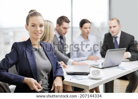 business, technology and office concept - smiling businesswoman with eyeglasses in office with team on the back - stock photo