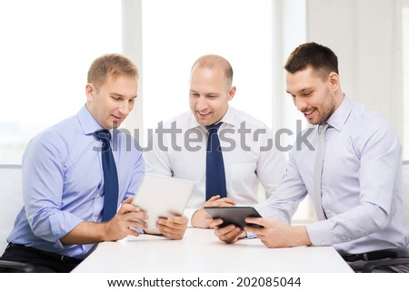 business, technology and office concept - three smiling businessmen with tablet pc computers in office