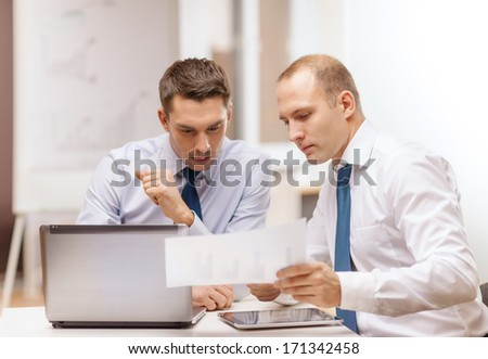 business, technology and office concept - two businessmen with laptop, tablet pc computer and papers having discussion in office - stock photo