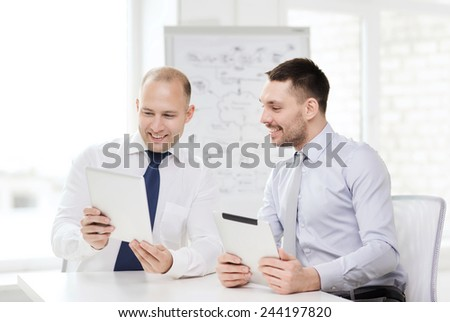 business, technology and office concept - two smiling businessmen with tablet pc computers in office - stock photo