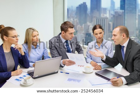 business, technology and people concept - business team with laptop computers, documents and coffee having discussion in office - stock photo