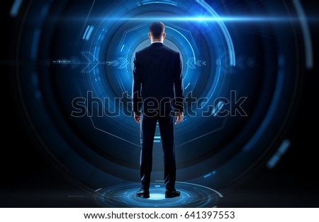 business, technology and people concept - businessman in suit and virtual projection over black background from back