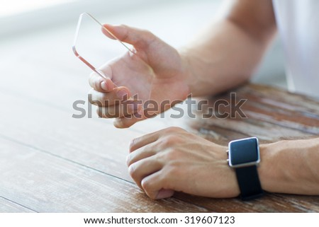 business, technology and people concept - close up of male hand holding and showing transparent smart phone and watch at home