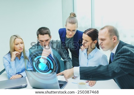 business, technology and people concept - serious business team with laptop computers and user icon projection having discussion in office - stock photo