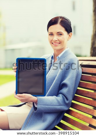 business, technology and people concept - young smiling woman with tablet pc computer sitting on bench in city