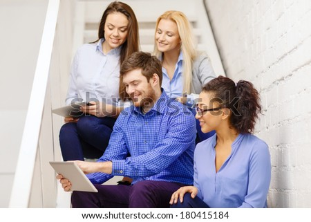 business, technology and startup concept - smiling creative team with tablet pc computer sitting on staircase
