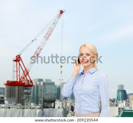 business, technology, building and people concept - smiling young businesswoman with smartphone over city building background
