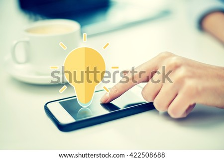 business, technology, communication, idea and people concept - close up of woman hand pointing finger to smartphone screen with lighting bulb icon in office - stock photo