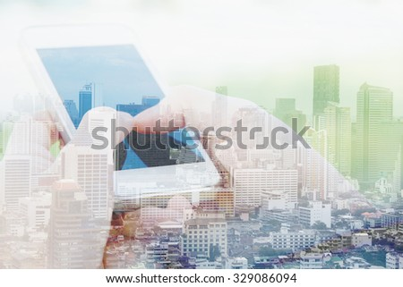 Business & technology concept. Double exposure of smart phone and cityscape background.
