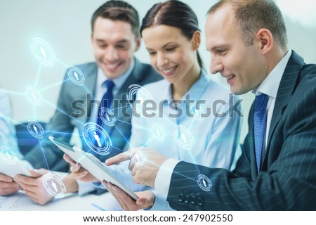 business, technology, connection, communication and people concept - smiling business team with tablet pc computer and virtual contacts projection having discussion in office - stock photo
