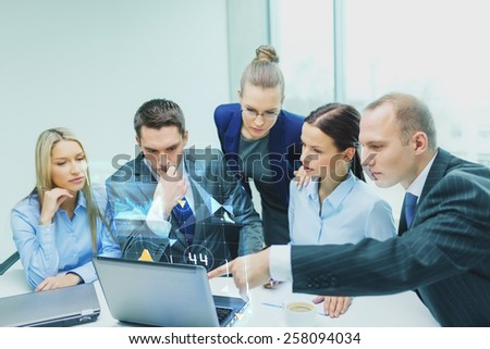 business, technology, development and people concept - serious business team with laptop computers and virtual graph projection discussion in office - stock photo