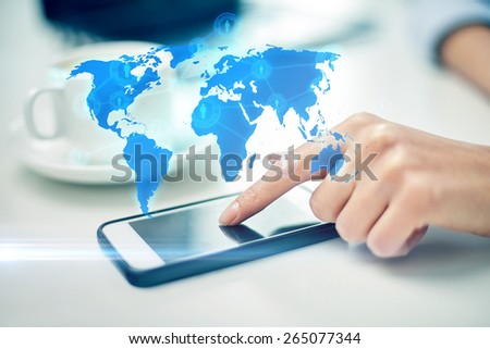 business, technology, global communication and people concept - close up of woman hand with smartphone and coffee pointing finger to screen over world map projection - stock photo