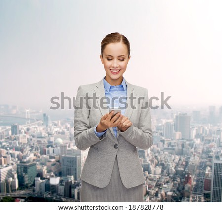 business, technology, internet and education concept - friendly young smiling businesswoman with smartphone - stock photo