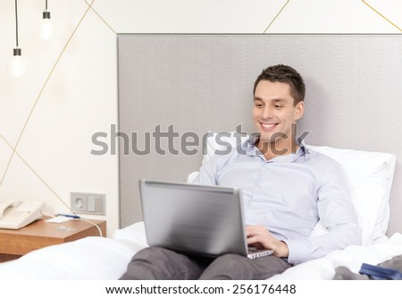 business, technology, internet and hotel concept - happy businessman with laptop computer lying in hotel in bed - stock photo