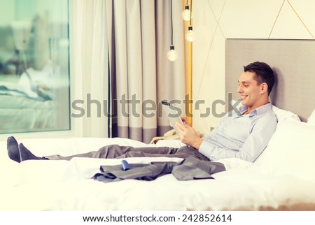 business, technology, internet and hotel concept - happy businessman with tablet pc computer lying in hotel in bed - stock photo