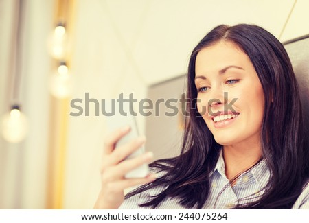 business, technology, internet and hotel concept - happy businesswoman with smartphone lying in hotel in bed - stock photo