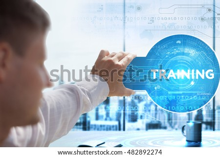 Business, Technology, Internet and network concept. Young businessman looks on a tablet, smart phone of the future. He sees the inscription: training