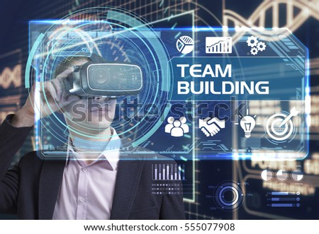 Business, Technology, Internet and network concept. Young businessman working in virtual reality glasses sees the inscription: team building