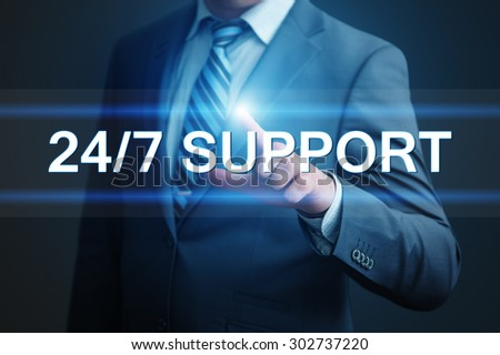 business, technology, internet and networking concept - businessman pressing 24/7 support button on virtual screens - stock photo