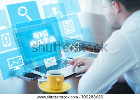 Business, technology, internet and networking concept. Young businessman working on his laptop in the office, select the icon big data on the virtual display. - stock photo