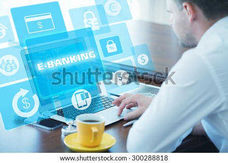 Business, technology, internet and networking concept. Young businessman working on his laptop in the office, select the icon e- banking on the virtual display - stock photo