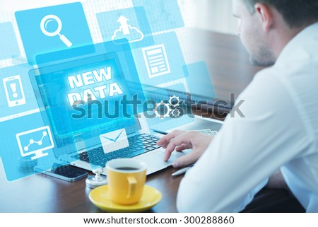 Business, technology, internet and networking concept. Young businessman working on his laptop in the office, select the icon new data on the virtual display - stock photo