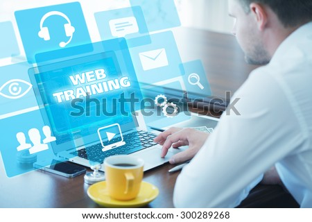 Business, technology, internet and networking concept. Young businessman working on his laptop in the office, select the icon web training on the virtual display. - stock photo