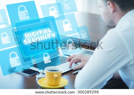 Business, technology, internet and networking concept. Young businessman working on his laptop in the office, select the icon digital security on the virtual display. - stock photo