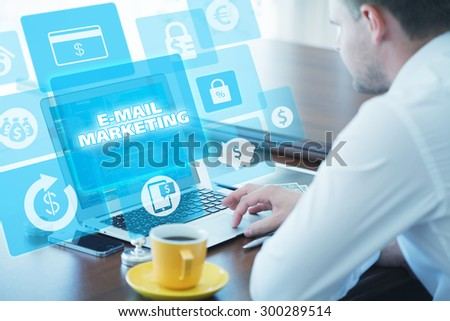 Business, technology, internet and networking concept. Young businessman working on his laptop in the office, select the icon e-mail marketing on the virtual display. - stock photo