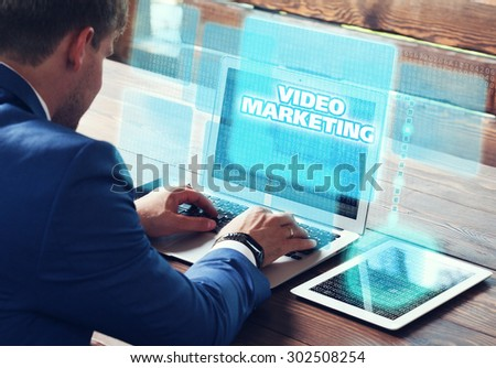 Business, technology, internet and networking concept. Young businessman working on his laptop in the office, select the icon video marketing on the virtual display. - stock photo