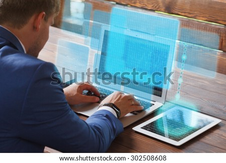 Business, technology, internet and networking concept. Young businessman working on his laptop in the office, select the icon on the virtual display. - stock photo