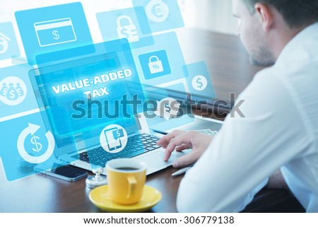 Business, technology, internet and networking concept. Young businessman working on his laptop in the office, select the icon value-added tax on the virtual display. - stock photo