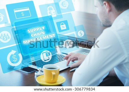 Business, technology, internet and networking concept. Young businessman working on his laptop in the office, select the icon supply chain management  on the virtual display. - stock photo
