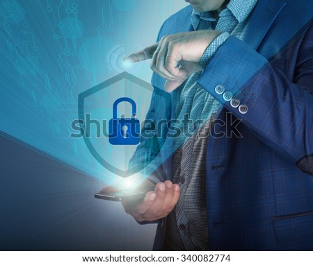 Business, technology, internet and networking concept. Young businessman working on his laptop in the office, select the icon security on the virtual display. - stock photo