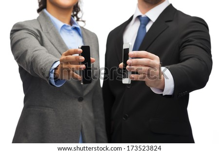 business, technology, internet and office concept - businessman and businesswoman with blank black smartphone screens in office