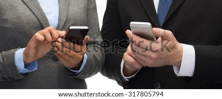 business, technology, internet and office concept - businessman and businesswoman with smartphones