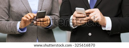 business, technology, internet and office concept - businessman and businesswoman with smartphones in office