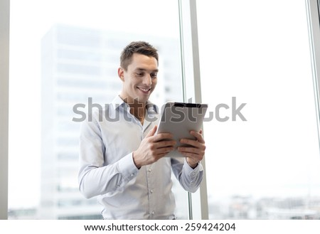 business, technology, internet and office concept - smiling businessman with tablet pc computer in office - stock photo